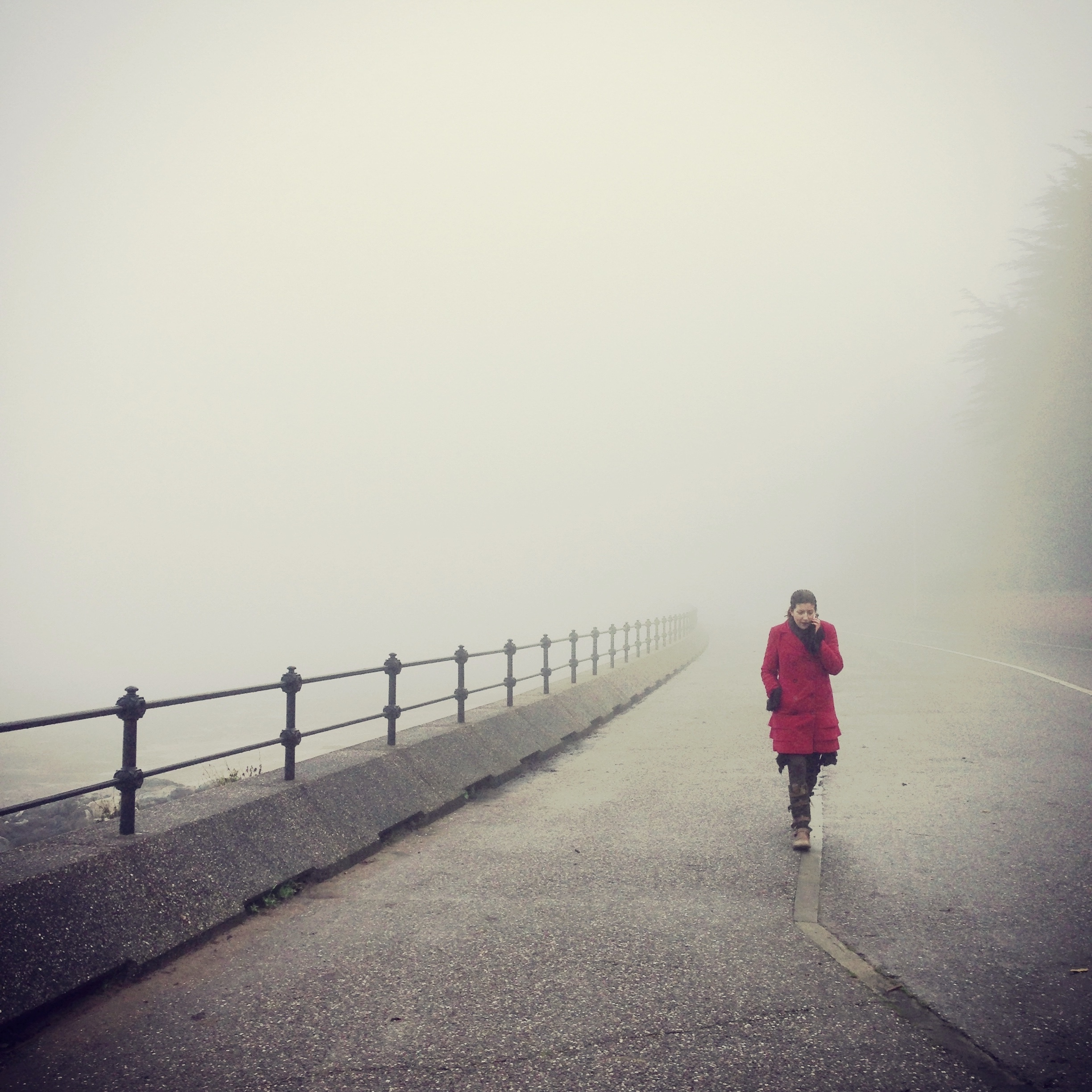 A woman in a red coat emerges from the fog by the river.